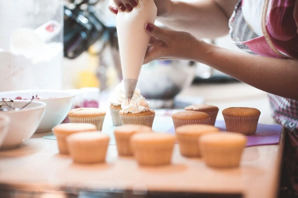 Photo of someone holding a pastry bag and putting white frosting on cupcakes